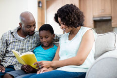 Parents reading book with their son in living room Royalty Free Stock Photos