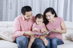 Parents reading story tale with their baby Royalty Free Stock Image