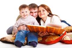 Parents reading to their kid Stock Photos