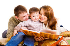 Parents reading to their kid Stock Photos