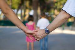 Parents retenant des mains avec des gosses dans l'avant Photos stock