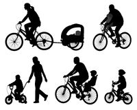 Parents riding bicycles with their kids Stock Images