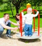 Parents rotating merrygoround Stock Photography