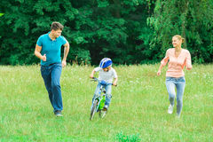 Parents Running With Their Son Riding A Bicycle stock photography