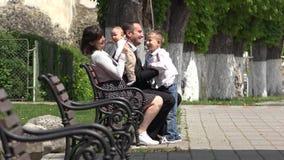 Parents s'asseyant sur le banc, mère se levant vers le haut du bébé, jeu de père avec un plus grand enfant, portrait heureux de f clips vidéos