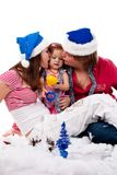 Parents in Santa's hat kissing their child Royalty Free Stock Photos