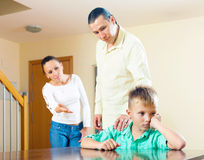 Parents scolding teenager son. Focus on boy. Parents scolding teenager son in home. Focus on boy only royalty free stock photography