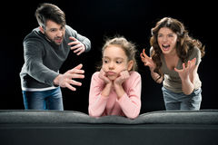 Parents screaming at little daughter on black, family problems concept. Aggressive parents screaming at little daughter on black, family problems concept Royalty Free Stock Photos