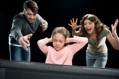 Parents screaming at little daughter closing ears with hands, family problems concept. Emotional parents screaming at little daughter closing ears with hands Stock Photos