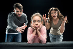 Parents screaming at scared little daughter looking at camera. Emotional parents screaming at scared little daughter looking at camera, family problems concept Royalty Free Stock Images