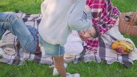 Parents se trouvant sur l'herbe - les enfants ont l'amusement et le fond courant dans le parc banque de vidéos