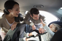 Parents securing baby in the car seat. In their car Stock Photography