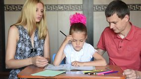 Parents show a child that she made mistakes doing homework stock video footage