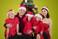 Parents sit with their sons near a Christmas tree. Picture of young parents sitting with their sons near a Christmas tree. Shot with green screen stock photo