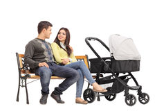 Parents sitting on a bench and talking to each other. Young parents sitting on a bench and talking to each other with a baby stroller next to them isolated on stock images