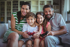 Parents sitting on sofa with their children and playing video games. At home Royalty Free Stock Image