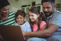 Parents sitting on sofa with their children and using laptop in living room Royalty Free Stock Image