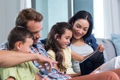 Parents sitting with son and daughter and looking at digital tablet stock photo