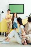 Parents sitting tied with rope on floor and smiling kids looking. At them royalty free stock photography