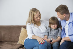Parents sitting with upset son on sofa at home Royalty Free Stock Photo