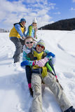 Parents on ski slope pulling children up hill on sled Stock Images