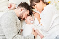 Parents sleep next to their little baby. Mother and father as happy parents sleep next to their little baby royalty free stock images