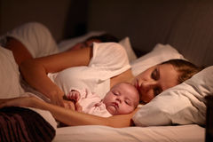 Parents Sleeping In Bed With Newborn Baby Stock Images