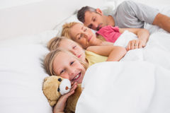 Parents sleeping with their daughters in bed Stock Image