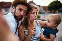 Parents and small toddler girl with ice cream outdoors in summer, taking selfie. Parents and small toddler girl with ice cream outdoors in summer, grimacing stock photos