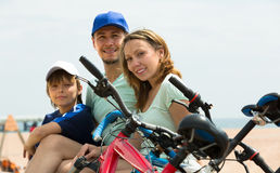 Parents and son with bicycles. Positive smiling parents and boy with bicycles at seashore Stock Photography