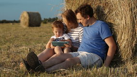 Parents and son in countryside with pad