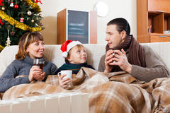 Parents and  son with cups of tea warming near warm calorifer Stock Image