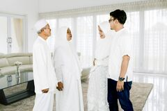 Parents with son and daughter talk together during Eid Mubarak celebration