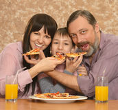 Parents with son eating pizza Stock Photo