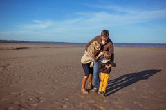 The parents and the son are embracing one another. Smiling parents and their five-year-old son are embracing one another at the beach. Clothes: casual royalty free stock image