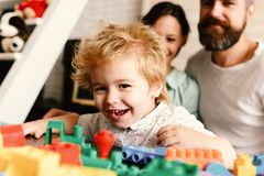Parents and son with happy faces make brick construction. Young family spends time in playroom. Mom and dad. Watch boy building out of plastic blocks on light royalty free stock images