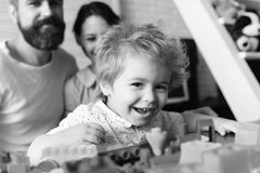 Parents and son with happy faces make brick construction. Young family spends time in playroom. Mom and dad. Watch boy building out of plastic blocks on light stock photos