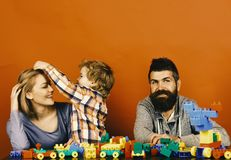 Parents and son with happy faces make brick constructions. Love and family games. Young family spends time in playroom. Parents and son with happy faces make royalty free stock image