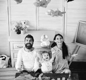 Parents and son with happy faces play with soft toys. Young family spends time in playroom. Mom, dad and boy throw toys up on light wooden background. Family royalty free stock photography