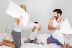 Parents and son having fun on bed in bedroom Stock Photos