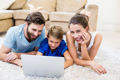 Parents and son lying on rug and using laptop. At home Royalty Free Stock Images