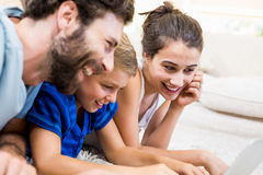 Parents and son lying on rug and using laptop. At home Royalty Free Stock Photos
