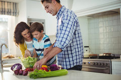 Parents and son preparing salad in the kitchen Stock Photo