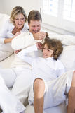 Parents and son relaxing on white sofa Stock Photos