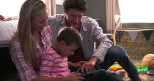 Parents And Son Sitting In Bedroom Using Digital Tablet stock footage