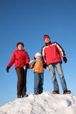 Parents with son on top of snowy hill Royalty Free Stock Images