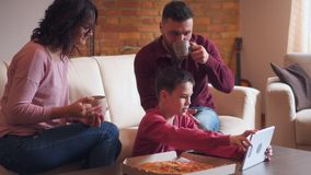 Happy family using digital tablet while having food and drink in living room stock footage
