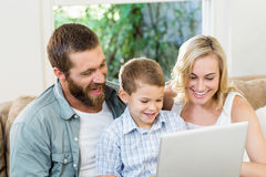 Parents and son using laptop in living room. At home Royalty Free Stock Image