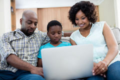 Parents and son using laptop in living room. At home Royalty Free Stock Photos