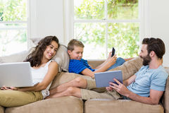 Parents and son using a laptop, tablet and phone Stock Photo